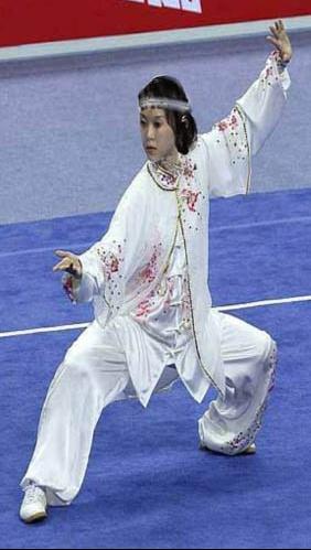 Luce dans un kata de wushu passant d'un Tim Bu à un Kong Bu, en costume Blanc d'apparat.