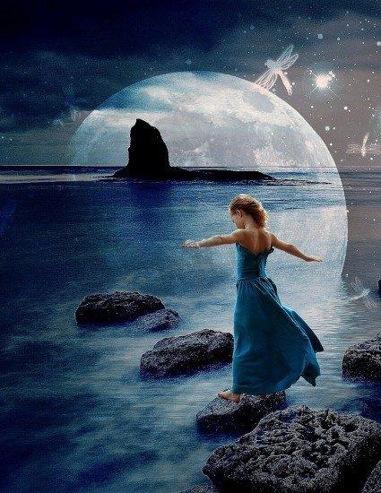 femme en robe bleue qui saute de rocher en rocher