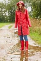 5531020-longueur-d-39-une-jeune-femme-heureuse-en-regle-impermeable-rouge-dans-une-flaque-d-39-eau-a