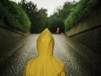 lena-johansson-a-person-wearing-a-yellow-raincoat-looking-up-a-cobble-stoned-street