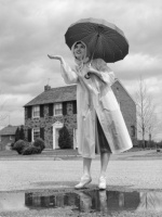 h-armstrong-roberts-woman-in-raincoat-and-rubber-boots-over-pumps-with-umbrella