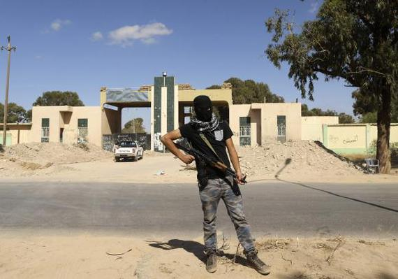 A militia stands guard in front of the entrance to the February 17 militia camp after Libyan irregul