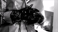 B&W video of woman in plastic wrap coat and black patent leather and suede gloves